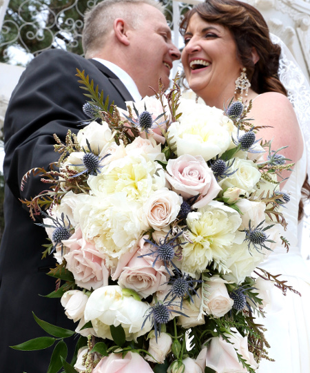 happy just married couple with large bouquet
